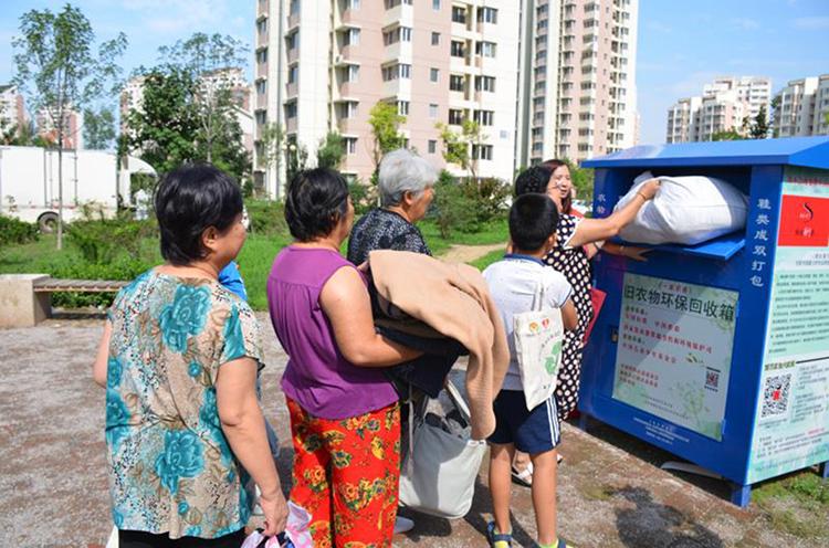 """天津市某社区居民有条不紊地把旧衣物放到一个""""蓝胖子""""里。.jpg"""