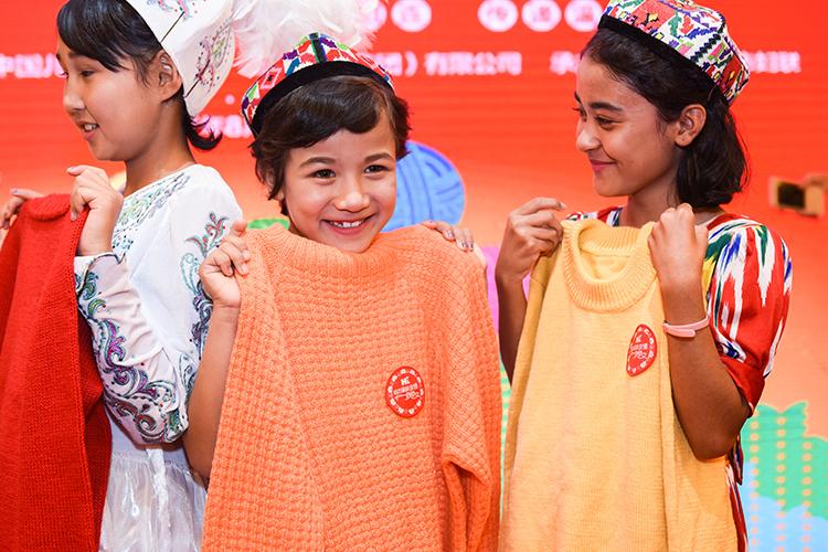 受助新疆儿童拿到爱心妈妈编制的毛衣露出甜甜的笑容.JPG