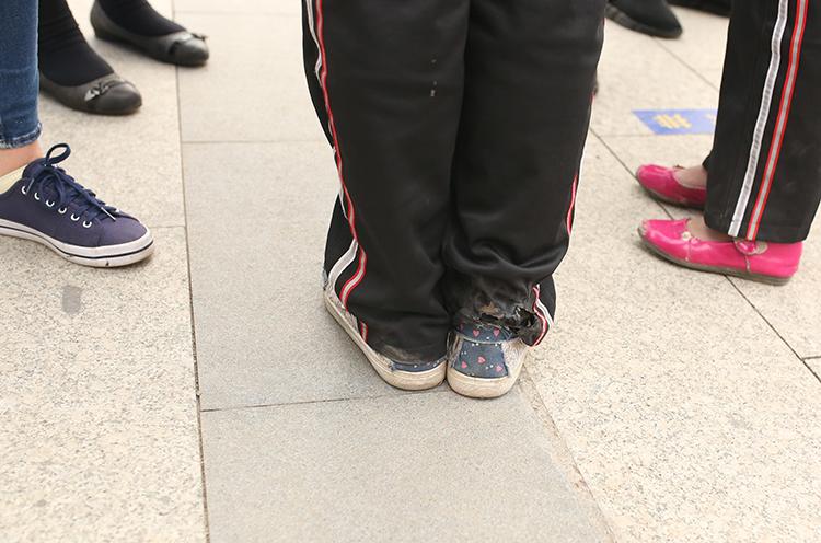 6.校服是张小蕾日常为数不多的衣服。因为长时间穿着,裤子的脚后跟处磨出两个破洞。脚上的运动鞋是她在学校里唯一的一双鞋。.JPG