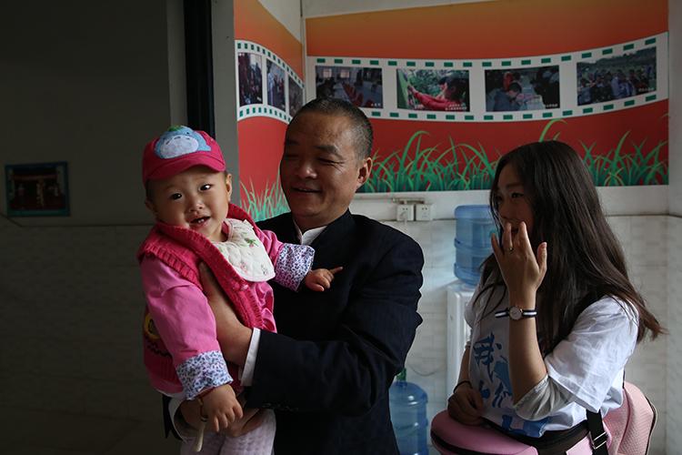 27岁的小欢带孩子回安康家园,园长胡源忠抱着孩子。.jpg