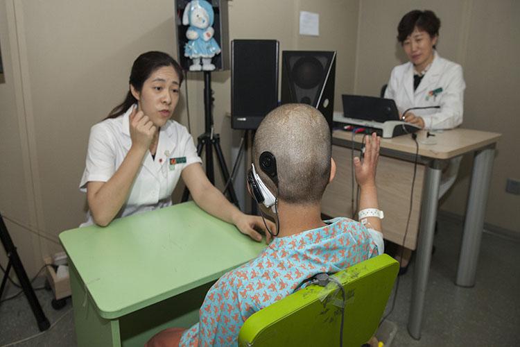 做完人工耳蜗植入手术的患儿与医生在沟通   魏星 摄.JPG