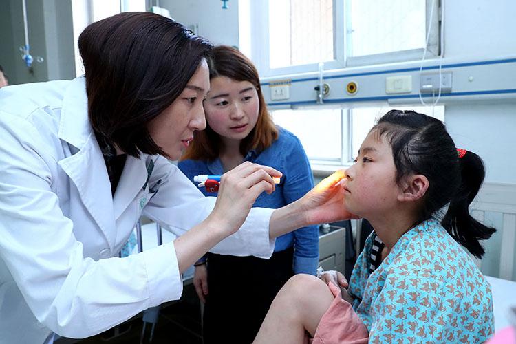 北京儿童医院医生为一名做完手术的视障孩子做检查 魏星 摄.jpg