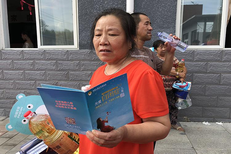村民在活动现场认真阅读关爱自闭症儿童科普读本.jpg