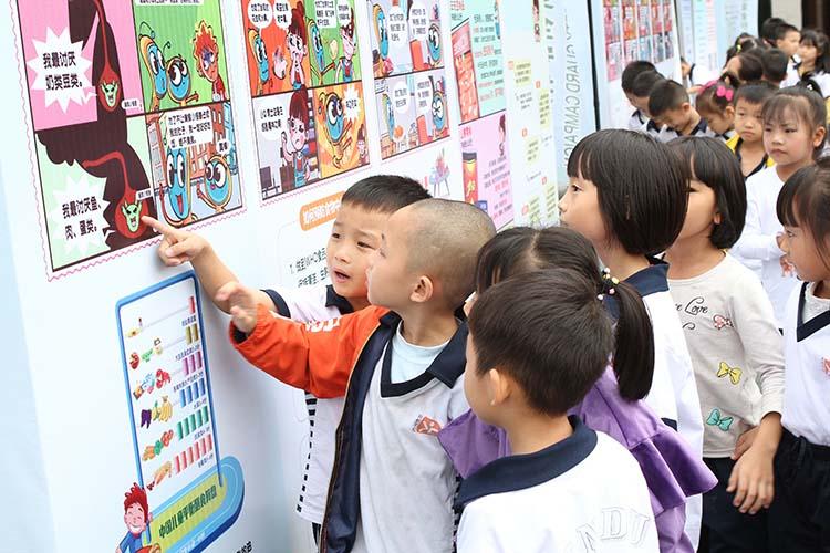 孩子们通过漫画展板学习食品安全知识.jpg