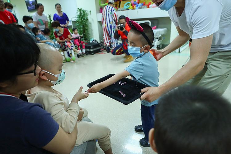 一名白血病患儿在工作人员的帮助下给小伙伴分发糖果.jpg